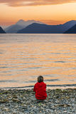 Woman enjoying beautiful sunset landscape on fjord. Woman enjoying beautiful landscape with sunset at the fjord, Norway Royalty Free Stock Image