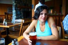Woman enjoying a beer Stock Image