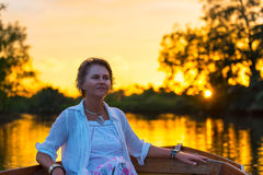 Woman  enjoying on boat at sunset on river Stock Photos
