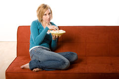 Woman enjoying bowl of popcorn. A view of a young woman casually dressed in jeans and comfortably curled up on a rust colored sofa or couch, enjoying a bowl of Stock Photography