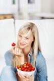 Woman enjoying a bowl of strawberries Stock Photo