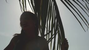 Cheerful young pretty woman enjoying bright tropical sun with sun flare effects in slow motion touching the palm tree. Woman enjoying bright tropical sun with stock video footage