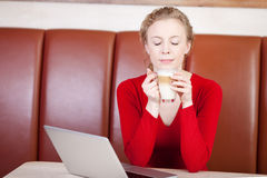 Woman enjoying caffee latte in café Stock Photography
