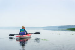 Woman enjoying a calm lake from the kayak Royalty Free Stock Photos