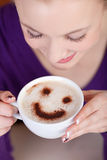 Woman enjoying cappuccino with a smile Stock Images