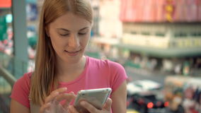 Woman Enjoying city street. Standing on bridge in urban city using smartphone. Road on background. Happy Smiling Young Woman Enjoying city street. Standing on stock footage