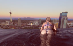 Woman enjoying the city view of Las Vegas from infinity pool. Back view of blonde woman enjoying the city view of Las Vegas at sunset from infinity pool Stock Image