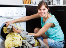 Woman enjoying clean clothes after laundry Stock Photos