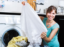 Woman enjoying clean clothes after laundry Stock Photography