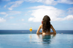 Woman enjoying cocktail in a swimming pool Royalty Free Stock Photography