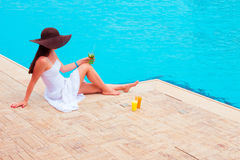 The woman enjoying cocktail in a swimming pool Stock Photography
