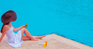 The woman enjoying cocktail in a swimming pool Royalty Free Stock Photography
