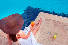 The woman enjoying cocktail in a swimming pool Stock Photos