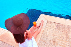 The woman enjoying cocktail in a swimming pool Royalty Free Stock Photos