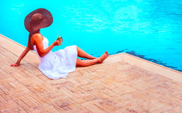 The woman enjoying cocktail in a swimming pool Royalty Free Stock Images