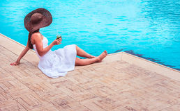 The woman enjoying cocktail in a swimming pool Stock Photo