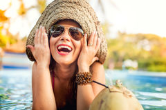 Woman enjoying a coconut alcoholic drink while at pool bar Royalty Free Stock Photography