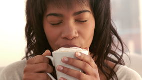 Woman enjoying coffee on couch stock video