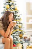 Woman enjoying coffee  near christmas tree Stock Photos