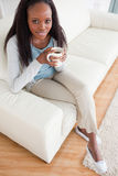 Woman enjoying coffee on sofa Stock Image