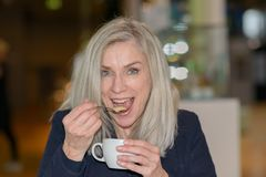 Woman enjoying coffee sucking on the teaspoon. Woman enjoying a cup of coffee sucking on the teaspoon with a twinkle in her eye as she looks at the camera stock images