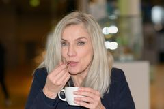Woman enjoying coffee sucking on the teaspoon. Woman enjoying a cup of coffee sucking on the teaspoon with a twinkle in her eye as she looks at the camera royalty free stock photography