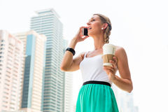 Woman enjoying coffee to go in metropolitan city Royalty Free Stock Photo