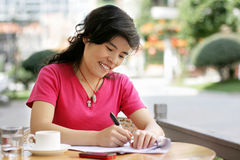 Woman enjoying a coffee and writing Stock Image