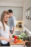 Woman enjoying cooking with man watching Stock Image