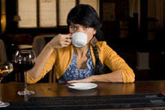 Woman enjoying a cup of coffee in a bar. Drinking from the cup and peering over the rim at the camera stock photos