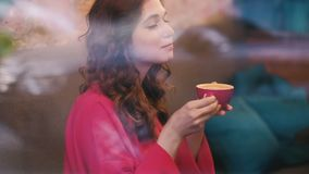 Woman enjoy coffee cafe glass drink latte. Woman enjoying cup of coffee in cafe behind the glass. Cute girl drinking hot latte or cappuccino in a red mug stock video