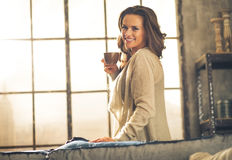Woman enjoying cup of coffee in loft apartment Stock Image