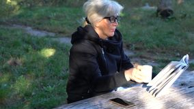 Woman enjoying a cup of coffee while reading. A book outdoors at a rustic wooden table in the shade of a tree in the garden stock video footage