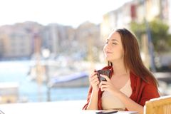 Woman enjoying a cup of coffee on vacation. Happy woman enjoying a cup of coffee in a restaurant on vacation on the beach Stock Photos