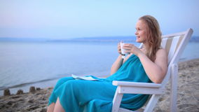 Woman enjoying a cup of tea at the seaside Stock Image