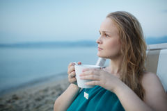 Woman enjoying a cup of tea at the seaside Royalty Free Stock Photo
