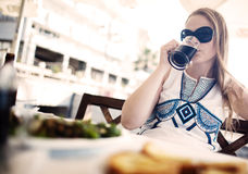 Woman enjoying a dark beer with her meal Stock Image