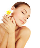 Woman enjoying day spa. Beautiful peaceful relaxed female, closed eyes, applying cream, hand massage, face with frangipani flower, healthy model isolated, girl Stock Photography