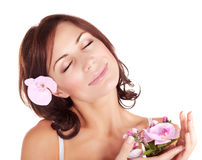 Woman enjoying dayspa. Photo of cute brunette girl with closed eyes enjoying dayspa, portrait of pretty young lady with pink orchid flower isolated on white Royalty Free Stock Images