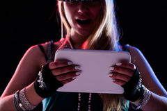 Woman enjoying digital content on a tablet. Girl or woman enjoying digital content on her tablet being online as like as she was really at the concert or event Stock Image