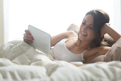 Woman enjoying with digital tablet in bed Stock Photos
