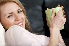 Woman enjoying drink on sofa Royalty Free Stock Image