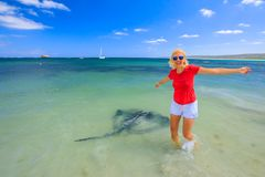 Woman enjoying Eagle Ray. Happy blonde woman with open arms near an Australian Eagle Ray close to shore in Hamelin Bay, Margaret River Region, Western Australia Royalty Free Stock Images