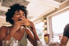 Woman enjoying eating burger at restaurant. African women eating stack burger at restaurant with friends. Happy young women having junk food at cafe with friends royalty free stock photos