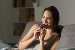 Woman enjoying eating chocolate in the night. Sitting on a couch in the living room at home Stock Photo