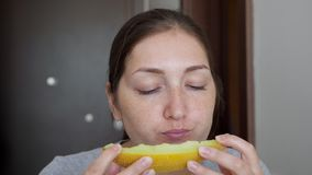 Woman is enjoying eating melon sitting at table on small kitchen. stock video footage