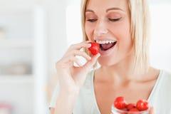 Woman enjoying eating strawberries Royalty Free Stock Image