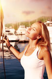 Woman enjoying energy of the sun. Beautiful blond female with closed eyes tanning under bright sunset light on the sail boat, happy  summer vacation Royalty Free Stock Photo