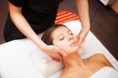 Woman enjoying a facial massage Stock Photography