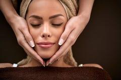Woman enjoying during facial massage in cosmetic salon Stock Image